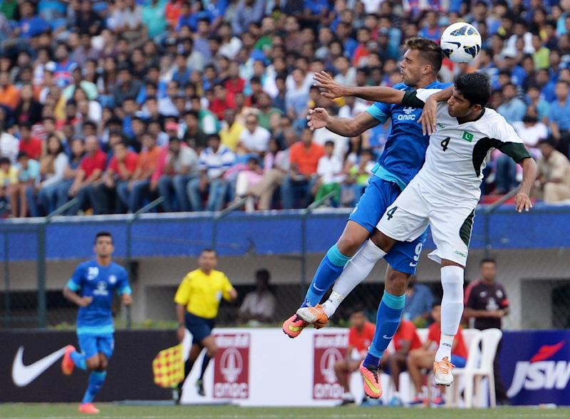 Indian forward Robin Singh (L) and Pakistani player Muhammad Bilal try to head the ball during a friendly football match in Bangalore at the Karnataka State Football Association Stadium in Bangalore on August 17, 2014