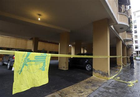 A Hezbollah flag is seen near the crime scene where commander Hasan al-Laqqis was killed in the southern Hadath district in Beirut December 4, 2013. REUTERS/Hasan Shaaban