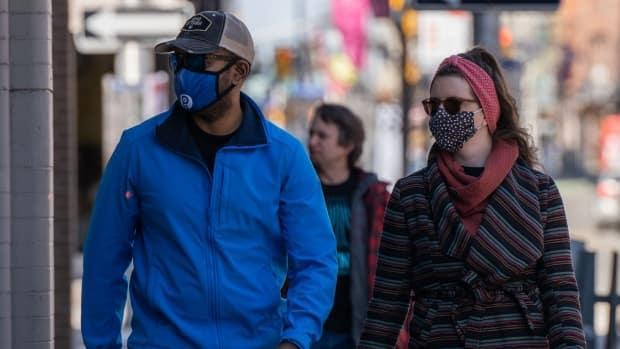 Two people wearing masks walk in downtown Ottawa on Saturday, April 3, 2021. (Mathieu Theriault/CBC - image credit)
