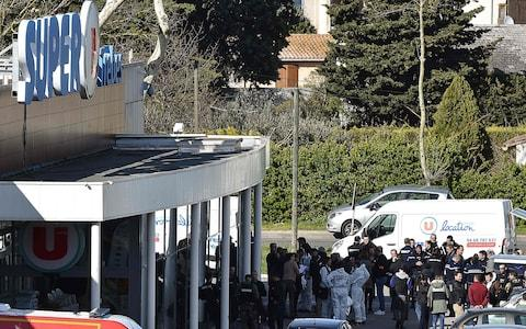 French security and police gather outside the Super U supermarket in the town of Trebes - Credit: PASCAL PAVANI/AFP