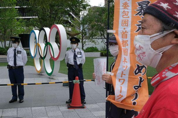 PHOTO: Security guards keep watch next to the Olympic Rings while people take part in a protest against the hosting of the 2020 Tokyo Olympic Games, in front of the headquarters building of the Japanese Olympic Committee in Tokyo, May 18, 2021. (Kazuhiro Nogi/AFP via Getty Images)