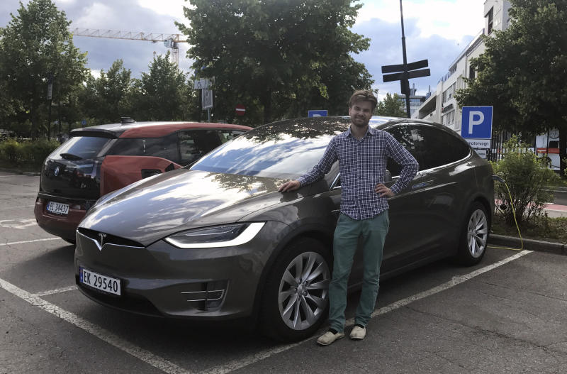 In this photo provided by Nils Henningstad, Henningstad poses next to his Tesla Model X while charging the electric car at a public charging station, Thursday, July 13, 2017, in Lillestrom, just outside Oslo, Norway. Electric cars are seeing growing support around the world. France and the United Kingdom want to ban sales of gas and diesel cars by 2040. But there's a problem: There aren't enough places to plug those cars in. (Lene Marie Brynildsen/Courtesy of Nils Henningstad via AP)
