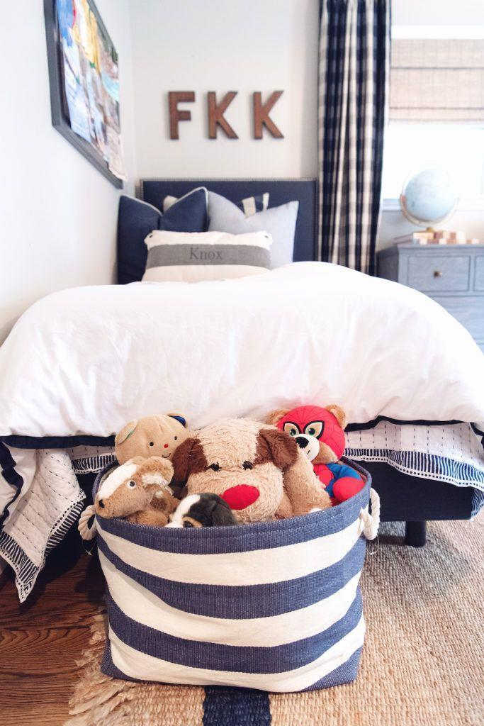 """<p>Place a fabric bin at the end of your child's bed to make storing stuffed animals a breeze at bedtime.</p><p><strong>See more at <a href=""""https://www.houseofharper.com/interiors/houston-home/the-boys-bedroom-update-2019/"""" rel=""""nofollow noopener"""" target=""""_blank"""" data-ylk=""""slk:House of Harper"""" class=""""link rapid-noclick-resp"""">House of Harper</a>.</strong></p><p><strong><a class=""""link rapid-noclick-resp"""" href=""""https://go.redirectingat.com?id=74968X1596630&url=https%3A%2F%2Fwww.containerstore.com%2Fs%2Fstorage%2Fdecorative-bins-baskets%2Fnavy-ivory-rugby-stripe-storage-bin-with-rope-handles%2F12d&sref=https%3A%2F%2Fwww.redbookmag.com%2Fhome%2Fg36014277%2Ftoy-organizer-ideas%2F"""" rel=""""nofollow noopener"""" target=""""_blank"""" data-ylk=""""slk:SHOP STRIPE BASKET"""">SHOP STRIPE BASKET</a><br></strong></p>"""