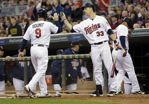 Minnesota Twins catcher Ryan Doumit, left, is congratulated by teammate Justin Morneau, center, as he and Oswaldo Arcia, right, score on a two-run single by Joe Mauer off Baltimore Orioles pitcher Jason Hammel in the second inning of a baseball game on Friday, May 10, 2013, in Minneapolis. (AP Photo/Jim Mone)