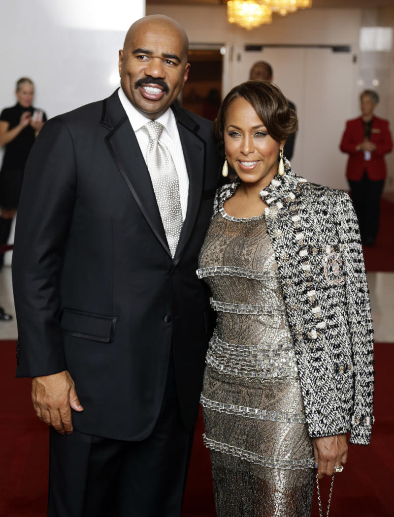 Entertainer Steve Harvey, left, with his wife Marjorie Bridges pose for photographers on the red carpet before entertainer Ellen DeGeneres receives the 15th annual Mark Twain Prize for American Humor at the Kennedy Center, Monday, Oct. 22, 2012, in Washington. (AP Photo/Alex Brandon)