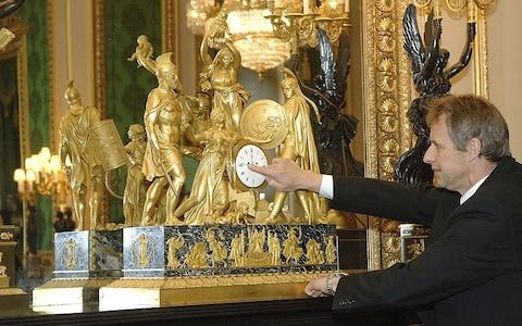 One down, 900 odd to go: A member of the Queen's staff at Windsor Castle adjusts a clock from the Royal Collection - Credit: Royal Collection Trust / © Her Majesty Queen Elizabeth II 2015