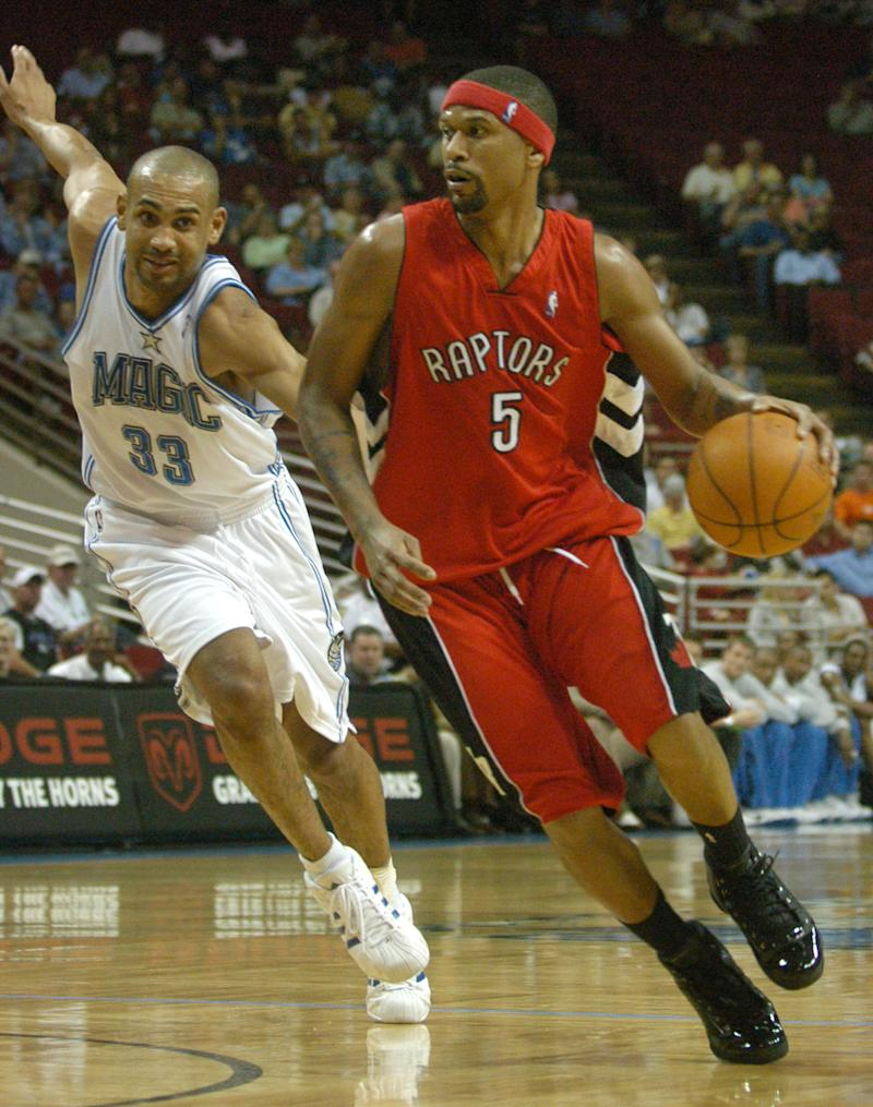 """FILE - In this Wednesday, March 30, 2005 file picture, Toronto Raptors guard Jalen Rose, right, drives past Orlando Magic forward Grant Hill during the first half of the game in Orlando, Fla. Basketball stars Jalen Rose and Grant Hill are going head to head _ but this time, they're not competing on the court. When Rose said he had considered black Duke University players like Hill """"Uncle Toms,"""" Hill responded with a blog posting that went viral in March 2011 _ and exposed a sensitive and longstanding issue for many African-Americans. If blacks have success in a white man's world, and do not conform to assumptions of how blacks should act, are they less black? (AP Photo/Phelan M. Ebenhack)"""