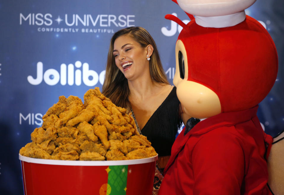 Miss Universe 2017 Demi-Leigh Nel-Peters of South Africa poses with a bucket of fried chicken during her interaction with Filipino orphans in her visit to the country's fast food chain Jollibee, along with other Miss Universe winners on 7 December, 2017, in suburban Pasay city south of Manila, Philippines. (AP file photo)