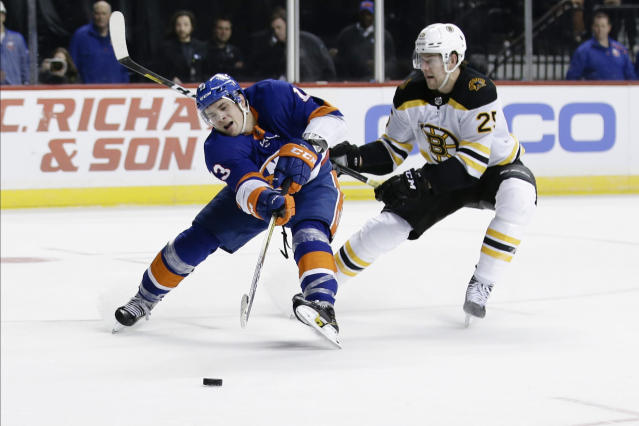 Boston Bruins' Brandon Carlo (25) defends New York Islanders' Mathew Barzal (13) during the second period of an NHL hockey game Saturday, Jan. 11, 2020, in New York. (AP Photo/Frank Franklin II)