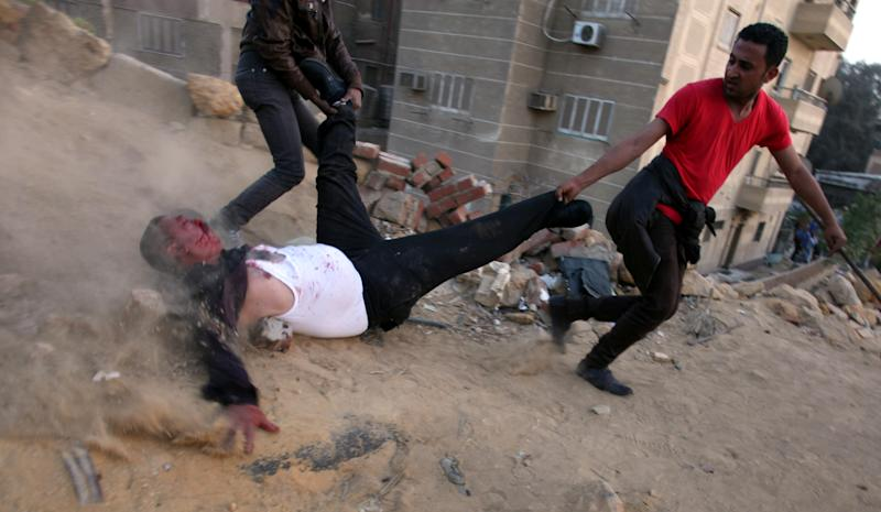 """FILE - In this Friday, March 22, 2013 file photo, Egyptian protesters drag a wounded Muslim Brotherhood supporter during clashes between supporters and opponents of Egypt's powerful Muslim Brotherhood near the Islamist group's headquarters in Cairo, Egypt. Known as the """"Battle of the Mountain,"""" a ferocious recent fight between members of Egypt's Muslim Brotherhood and their opponents in Cairo is looking like a dangerous turning point in the country's political turmoil. Some protesters showed a new willingness to turn to violence against Islamists they accuse of dominating Egypt, while Islamists have heightened their calls for action against opponents they accuse of trying to topple the president. (AP Photo/Khalil Hamra, File)"""