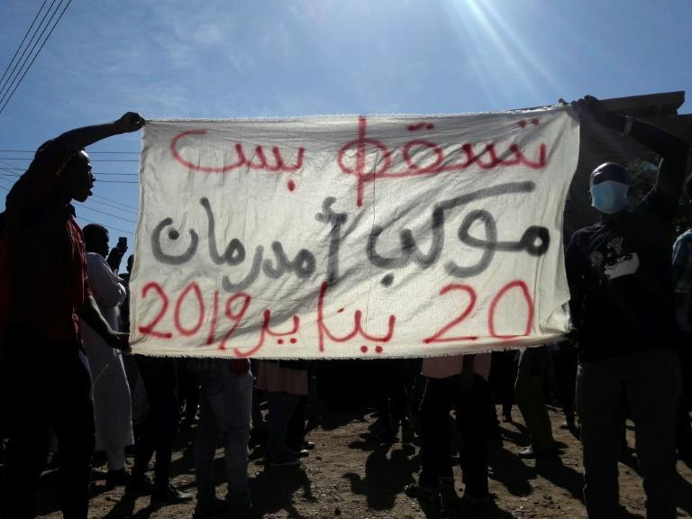 Sudanese demonstrators hold up a banner calling for the overthrow of the regime during an anti-government protest in Khartoum's twin city Omdurman on January 20, 2019