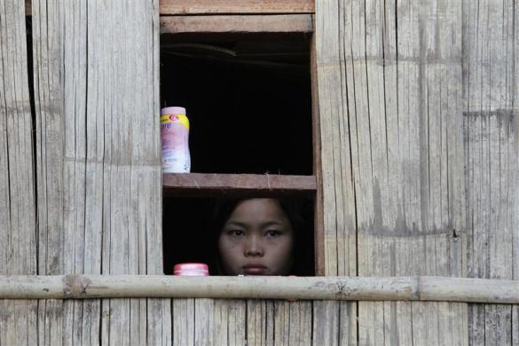 A child watches a ceremony outside her window during the 63rd anniversary of Karen Revolution Day at Oo Kray Kee Township in the Karen State, along the Thai-Myanmar border, January 31, 2012.