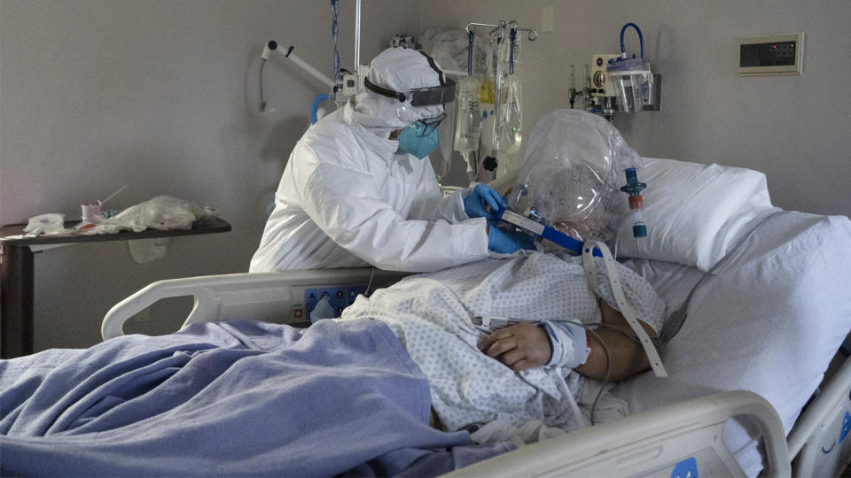 A member of the medical staff treats a patient who is wearing a helmet-based ventilator
