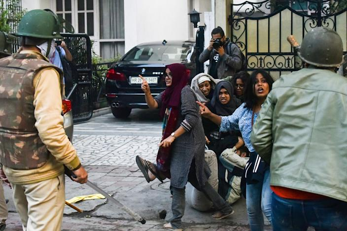 In this picture taken on December 15, 2019, Ayesha Renna (C) and other protesters argue with policemen during a demonstration against the Indian government's Citizenship Amendment Bill (CAB) in New Delhi. A group of Muslim woman who formed a human barricade around a male student being attacked by baton-swinging police are becoming icons in the protests currently gripping India. (Photo by STRINGER / AFP) /