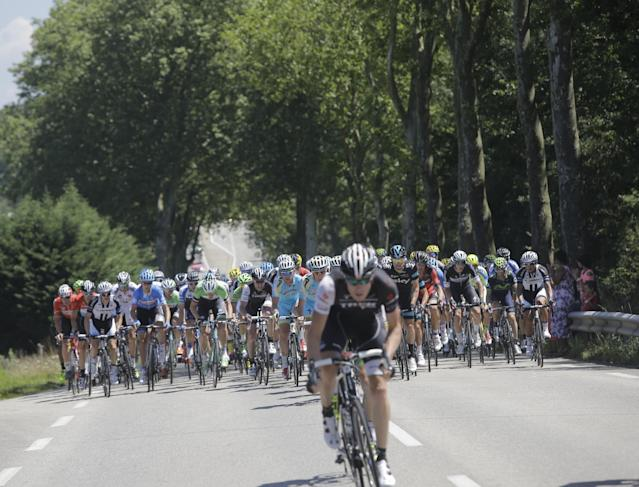 Switzerland's Gregory Rast, front, breaks away from the pack, rear, during the twelfth stage of the Tour de France cycling race over 185.5 kilometers (115.3 miles) with start in Bourg-en-Bresse and finish in Saint-Etienne, France, Thursday, July 17, 2014. (AP Photo/Laurent Cipriani)