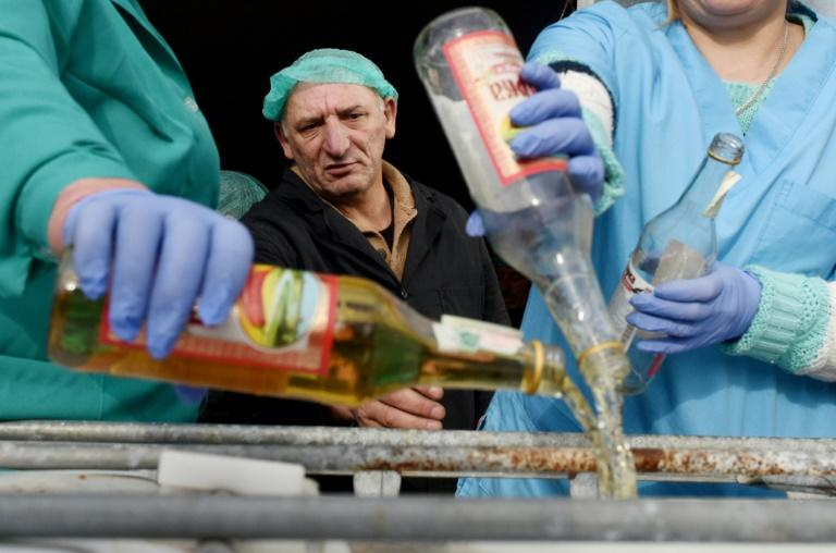 A supervisor looks on as workers empty bottles of the adulterated vodka in the town of Vynnyky, western Ukraine