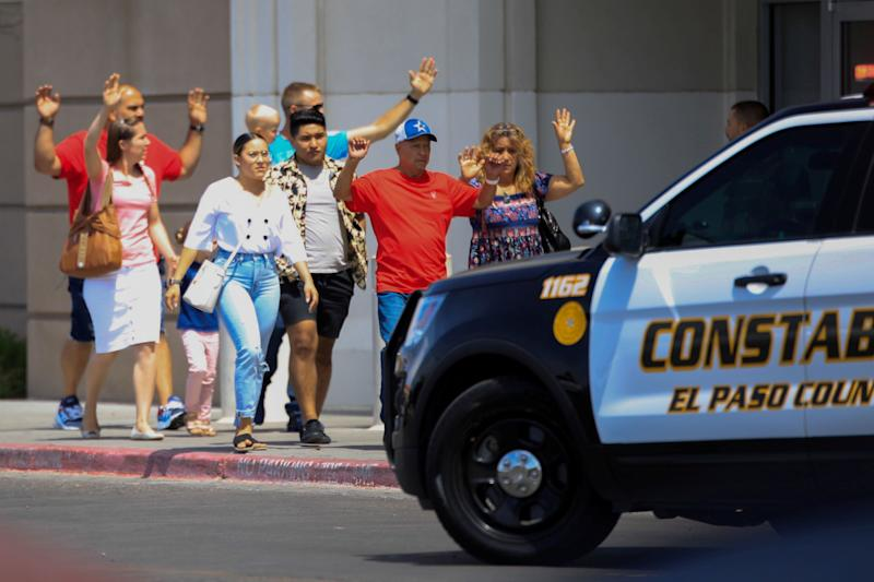 Shoppers exit with their hands up after a mass shooting at a Walmart in El Paso, Texas, on Aug. 3. The store chain has since changed its policy on carrying guns in its stores. (Photo: Jorge Salgado / Reuters)