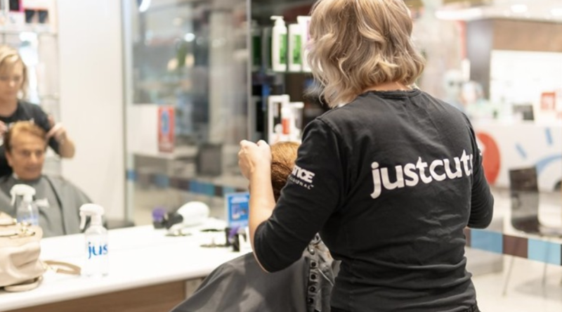 A female Just Cuts hairdressers cuts a man's hair in a Just Cuts salons in Randwick, Sydney.
