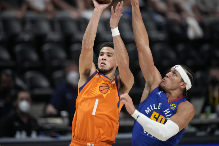 Phoenix Suns guard Devin Booker shoots as Denver Nuggets forward Aaron Gordon defends during the first half of Game 3 of an NBA second-round playoff series Friday, June 11, 2021, in Denver. (AP Photo/David Zalubowski)