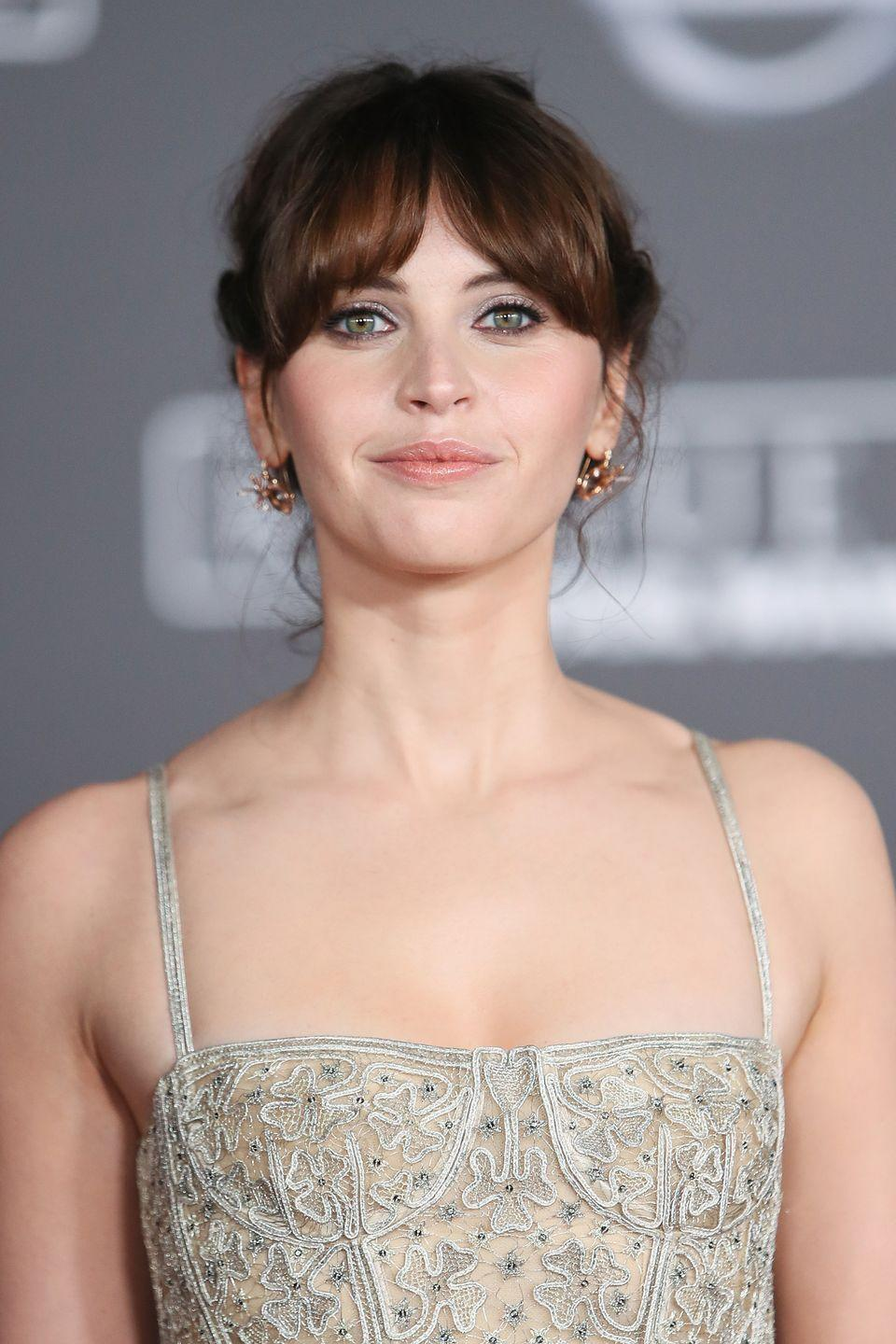 <p>Felicity Jones' face is almost triangular in shape, so this curtained fringe is a nice way of concealing a broader forehead, allowing the eye to focus on her slender jaw. </p>