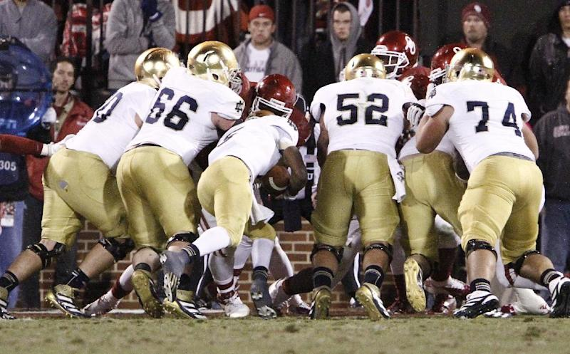 Notre Dame quarterback Everett Golson, center, dives in for a touchdown against Oklahoma during the fourth quarter of an NCAA college football game in Norman, Okla., Saturday, Oct. 27, 2012. Notre Dame won 30-13. (AP Photo/Alonzo Adams)