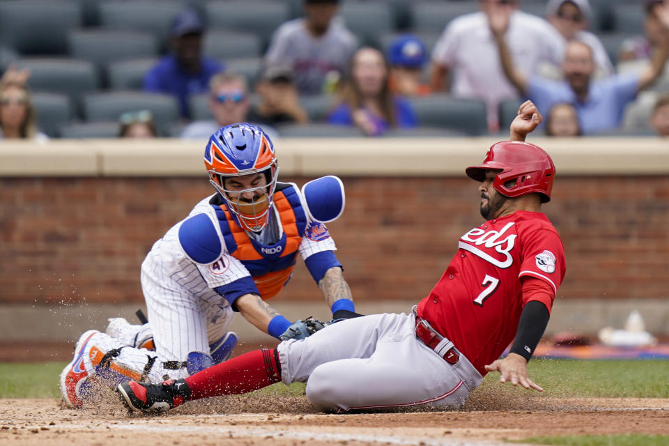 New York Mets catcher Tomas Nido, left, tags out Cincinnati Reds Eugenio Suarez (7) at home after a hit by Tyler Naquin during the fourth inning of a baseball game, Sunday, Aug. 1, 2021, in New York. (AP Photo/Corey Sipkin)