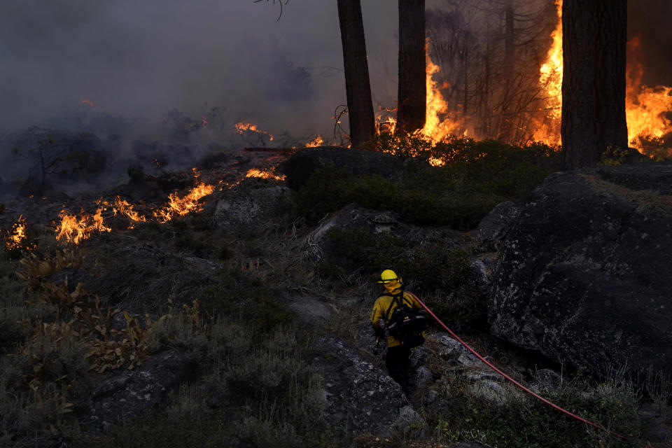 FILE - In this Sept. 2, 2021, file photo, a firefighter carries a water hose toward a spot fire from the Caldor Fire burning along Highway 89 near South Lake Tahoe, Calif. An unidentified firefighter has died of an illness while assigned to one of California's largest wildfires, authorities said Sunday, marking the first death in a season that has seen blazes destroy thousands of buildings and force entire towns to flee. Edwin Zuniga with the California Department of Forestry and Fire Protection said he couldn't provide other details on the death. (AP Photo/Jae C. Hong, File)