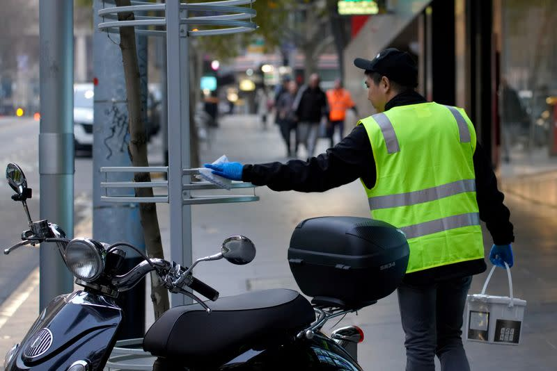An essential worker sanitises surfaces under COVID-19 lockdown restrictions in Melbourne