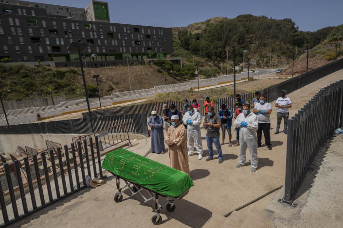 Ceuta residents and migrants perform a funeral prayer on a Moroccan teenager in the muslim cemetery at the Spanish enclave of Ceuta, Saturday, May 22, 2021. The young man died on Monday trying to swim across the border from Morocco to Spain's North Africa enclave with thousands of other migrants. (AP Photo/Bernat Armangue)