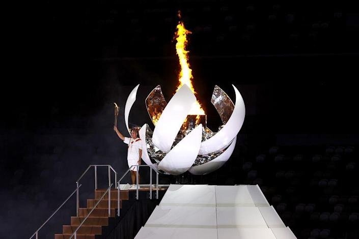 <p>Japanese Tennis star Naomi Osaka lights the Olympic cauldron with the Olympic torch during the opening ceremony.</p>