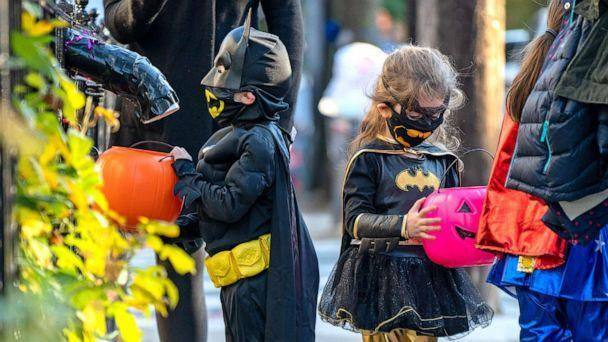 PHOTO: Children receive treats by candy chutes while trick-or-treating for Halloween in Woodlawn Heights on Oct. 31, 2020 in New York City. (David Dee Delgado/Getty Images, FILE)
