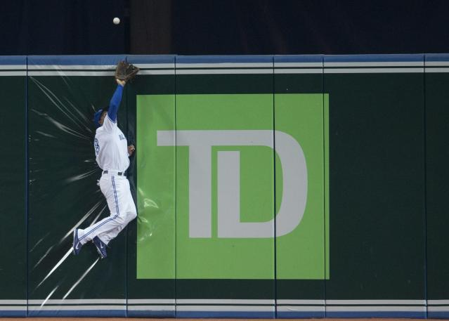 Toronto Blue Jays' Anthony Gose makes a leaping catch at the wall to rob Tampa Bay Rays' James Loney of a hit during the third inning of a baseball game in Toronto on Wednesday, May 28, 2014. (AP Photo/The Canadian Press, Darren Calabrese)