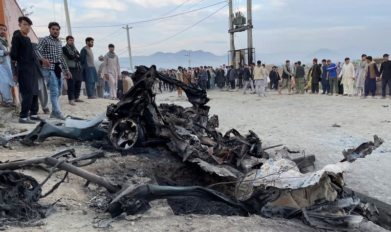 People stand at the site of a blast in Kabul