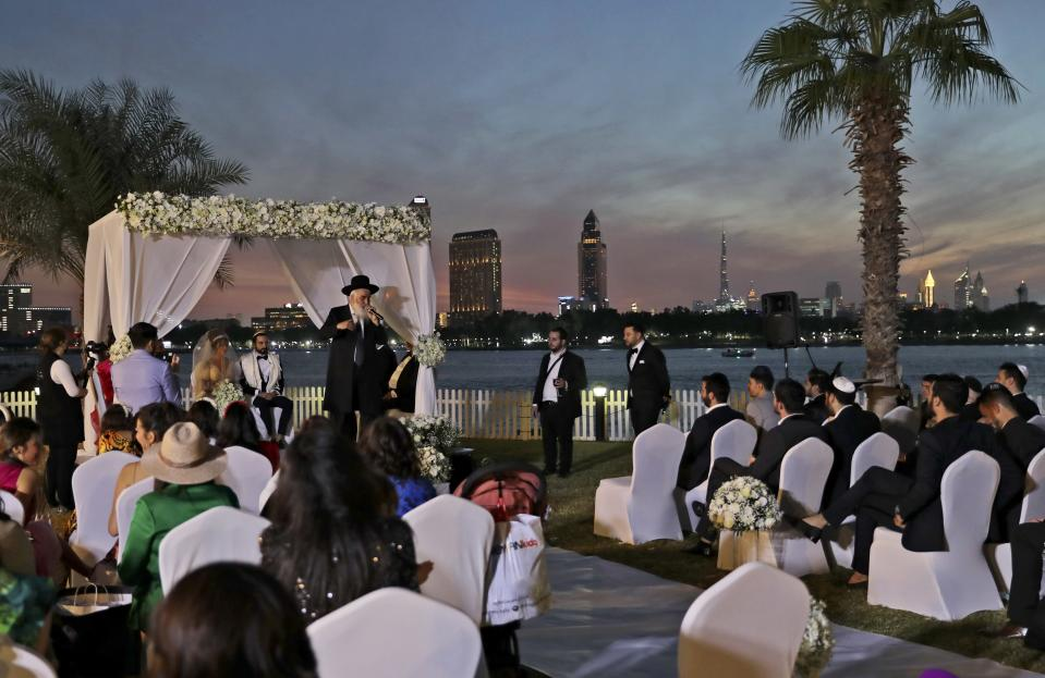 A rabbi officiates under a traditional Jewish wedding canopy during marriage ceremony of the Israeli couple Noemie Azerad, left sited under the canopy, and Simon David Benhamou, at a hotel in Dubai, United Arab Emirates, Thursday, Dec. 17, 2020. For the past month, Israelis long accustomed to traveling incognito, if at all, to Arab countries, have made themselves at home in the UAE's commercial hub.(AP Photo/Kamran Jebreili)