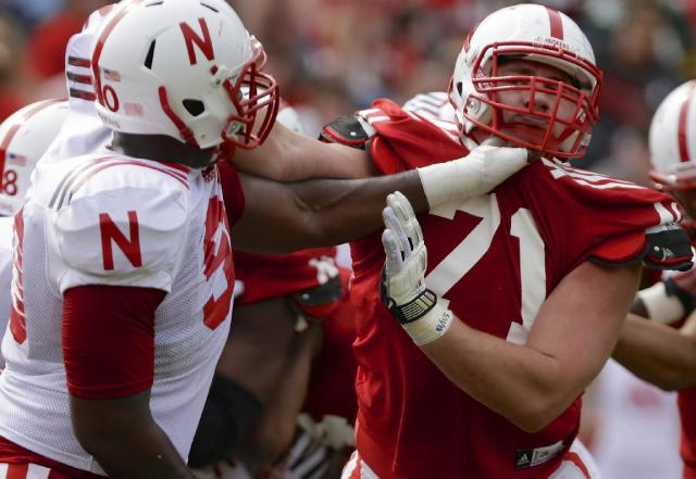 Nebraska defensive end Greg McMullen, left, faces Nebraska offensive lineman Alex Lewis, right, during an NCAA college football spring game in Lincoln, Neb., Saturday, April 12, 2014. (AP Photo/Nati Harnik)