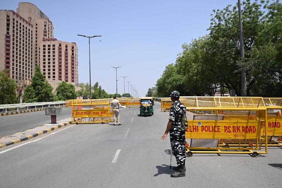 <p>Police personnel at a checkpoint during a weekend lockdown imposed by Delhi on 18 April, 2021.</p> (AFP via Getty Images)
