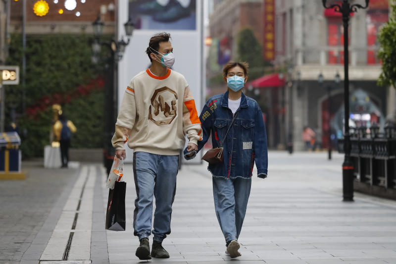 In this photo released by Xinhua News Agency, a couple wearing protective masks to prevent the new coronavirus outbreak walk on a re-opened commercial street in Wuhan in central China's Hubei province on Monday, March 30, 2020. Shopkeepers in the city at the center of China's virus outbreak were reopening Monday but customers were scarce after authorities lifted more of the anti-virus controls that kept tens of millions of people at home for two months. (Shen Bohan/Xinhua via AP)