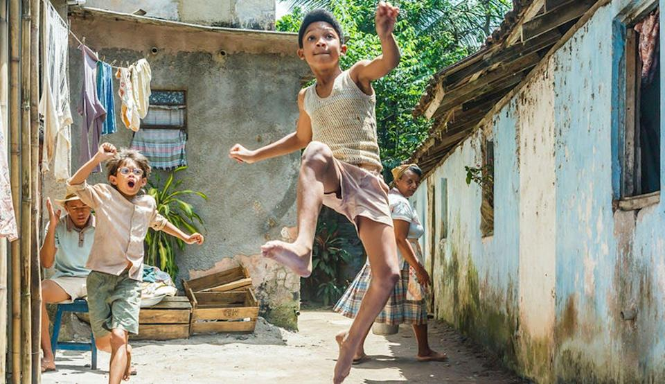 a young boy kicks his foot in the air