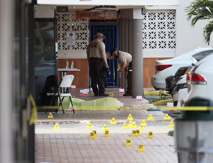 Miami-Dade police mark where shell casings fell in a mass shooting outside a banquet hall May 30 in Hialeah, Fla. Two people died, and more than 20 were injured.