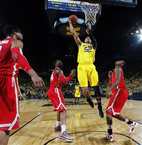 Michigan forward Jordan Morgan (52) shoots against Ohio State forward Jared Sullinger, far left, guard William Buford, second from left, and forward Deshaun Thomas, right, in the first half of an NCAA college basketball game, Saturday, Feb. 18, 2012, in Ann Arbor, Mich. (AP Photo/Tony Ding)