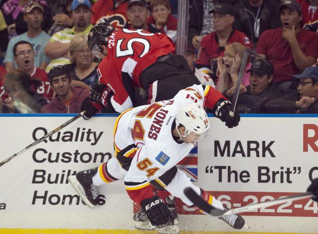 Ottawa Senators Michael Sdao and Calgary Flames forward David Jones collide during first period NHL pre-season action on Monday, Sept. 16, 2013 in Saskatoon, Saskatchewan. (AP Photo/The Canadian Press, Liam Richards)