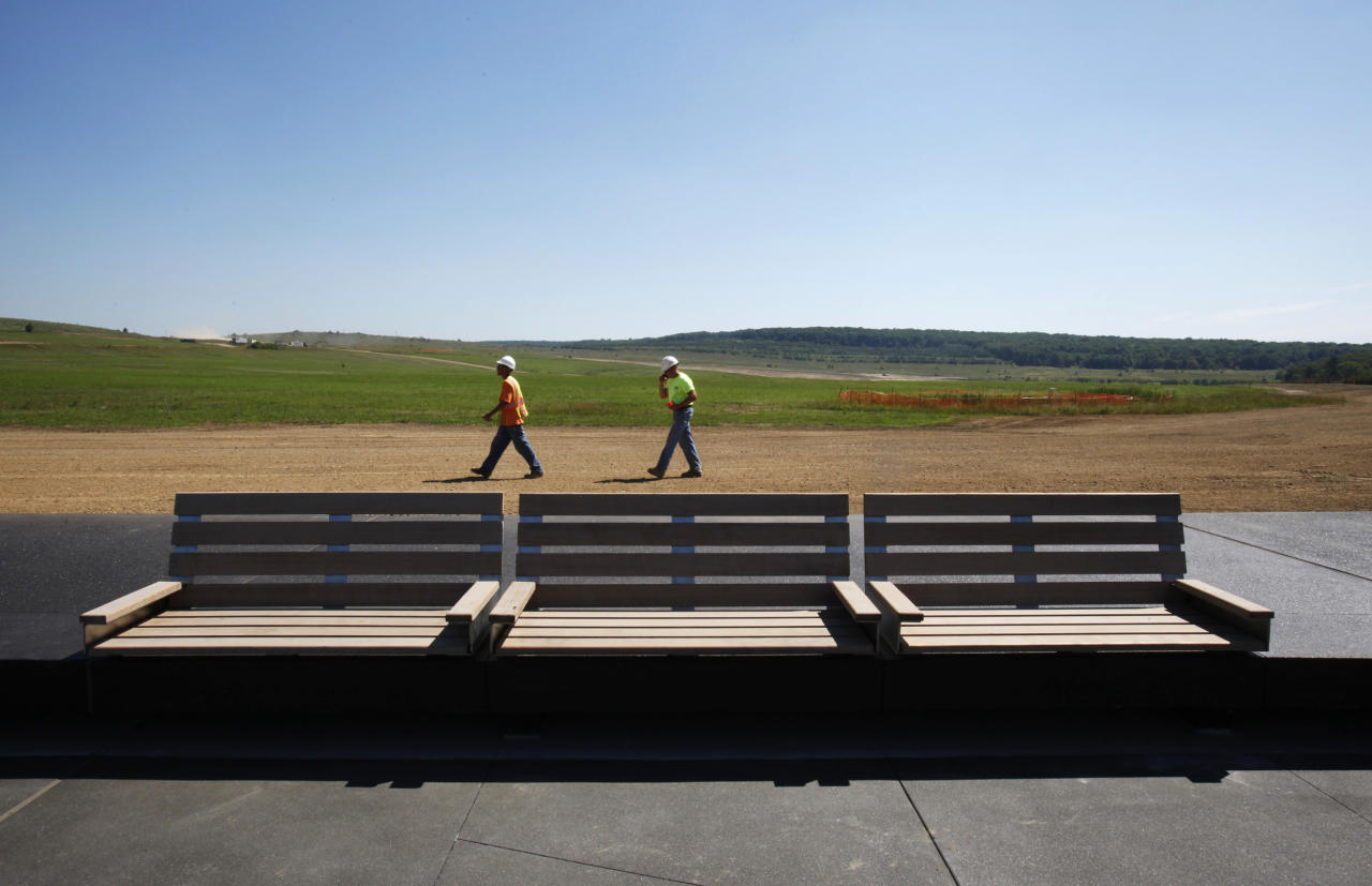 Construction workers Shawn Underwood (L) and Neil Hosick (R) walk behind the cement walkway at the Flight 93 National Memorial outside Shanksville, Pennsylvania July 6, 2011. The permanent memorial, will be dedicated this year on September 10, but will not be completed until 2014. (REUTERS/Jason Cohn)