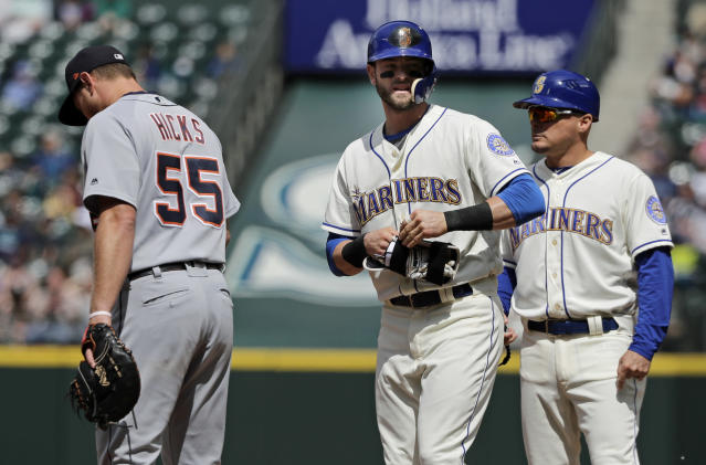 Seattle Mariners' Mitch Haniger, center, stands on first base next to Detroit Tigers first baseman John Hicks (55) and first base coach Chris Prieto, right, after hitting a single to break up a no-hitter in the seventh inning of a baseball game against the Detroit Tigers, Sunday, May 20, 2018, in Seattle. (AP Photo/Ted S. Warren)
