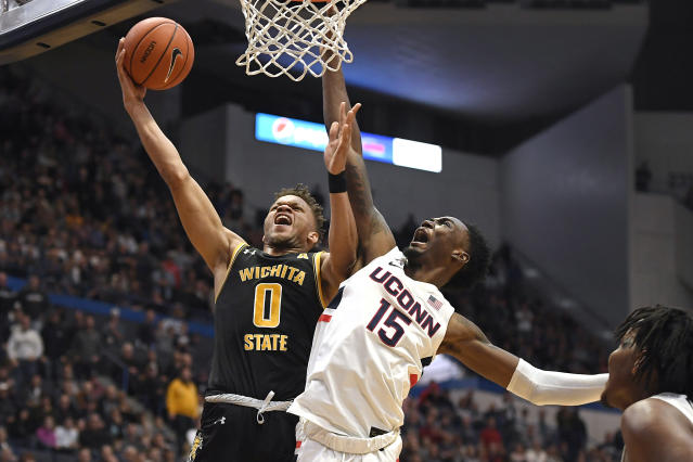 Wichita State's Dexter Dennis (0) shoots as Connecticut's Sidney Wilson (15) defends in the second half of an NCAA college basketball game, Sunday, Jan. 12, 2020, in Hartford, Conn. (AP Photo/Jessica Hill)