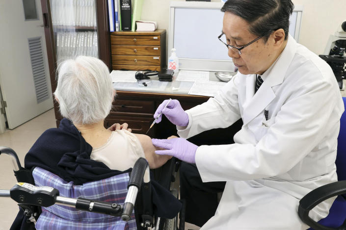 An elderly woman receives her first dose of Pfizer's COVID-19 vaccine at a special nursing home in Nagasaki, southwestern, Japan, Monday, April 12, 2021. Japan started its vaccination drive with medical workers and expanded Monday to older residents, with the first shots being given in about 120 selected places around the country. (Kyodo News via AP)
