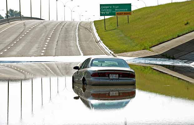 An abandoned car sits in the water on Whitemud Drive after heavt rain hit south Edmonton on July 12, 2012.