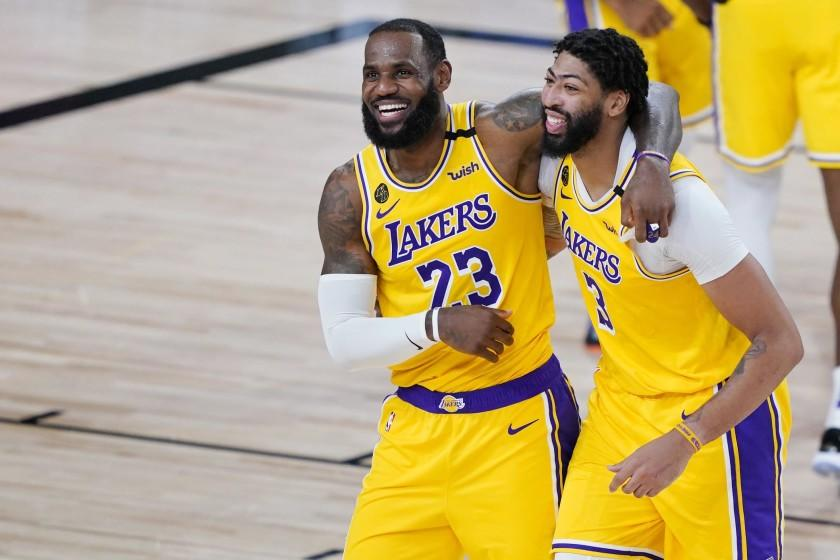 Los Angeles Lakers' LeBron James (23) and Anthony Davis (3) celebrate after defeating the Denver Nuggets 124-121 during an NBA basketball game Monday, Aug. 10, 2020, in Lake Buena Vista, Fla. (AP Photo/Ashley Landis, Pool)