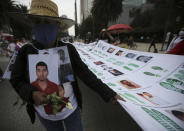 A person holds a portrait during a march in remembrance of those who have disappeared, on Mother's Day in Mexico City, Monday, May 10, 2021. (AP Photo/Fernando Llano)