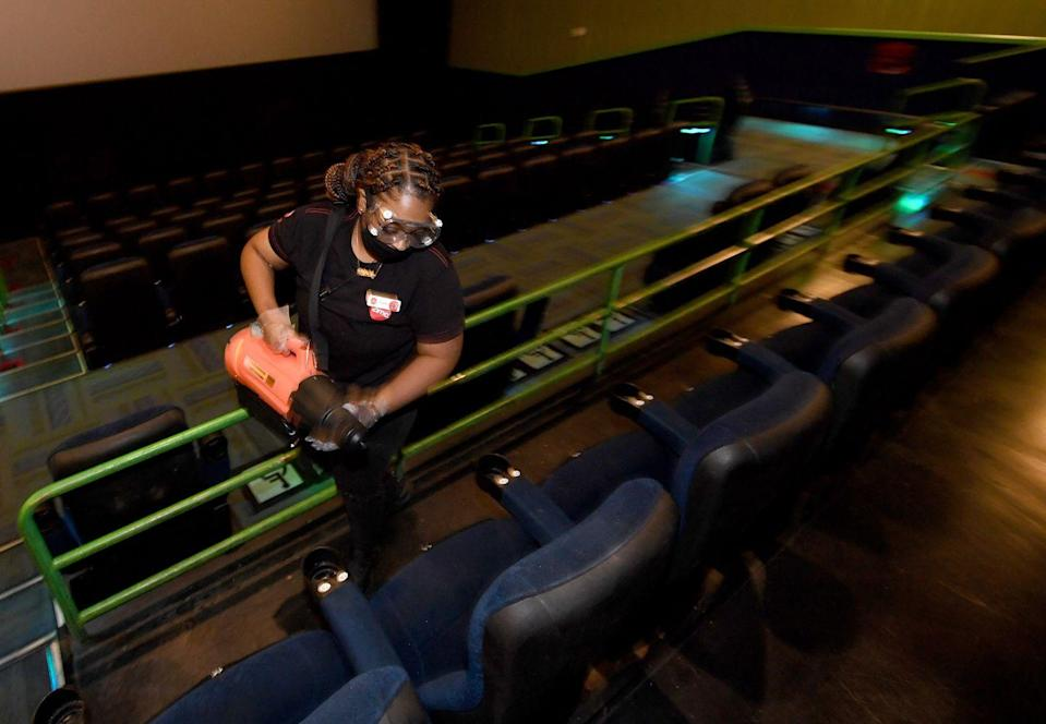 <p>Ajana Robertson uses an electrostatic disinfectant sprayer to sanitize auditorium seats after a show at AMC Town Square 18 on August 20 in Las Vegas, Nevada.</p>