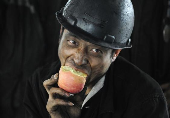 A miner eats an apple after his shift at a coal mine in Xiaoyi, Shanxi province June 27, 2010.